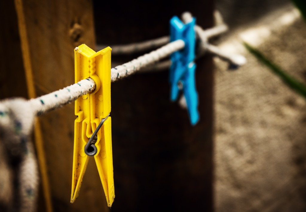 Two different wash pins yellow and blue hanging on rope on vintage background.